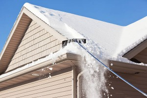A roof rake is being used to remove snow from a winter roof. Large amounts of snow are often removed, using this method, to prevent ice dams and reduce excess weight. Ice dams form when melted roof snow freezes at the gutter sometimes leading to damage to the roof edge.
