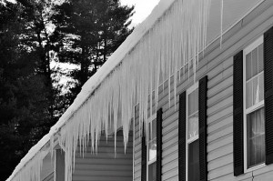 Long heavy icicles posing an ice damage risk to the burdened eaves of a building after a severe winter storm.